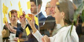 Geschäftsleute machen Notizen auf Zetteln an einer Wand aus Glas