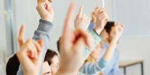 Viele Schüler heben ihre Hände im Unterricht